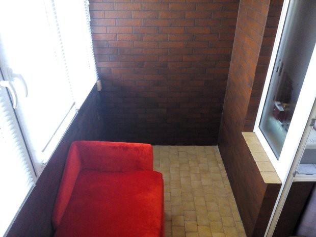 Балкон с красным угловым диваном и стенами под кирпич