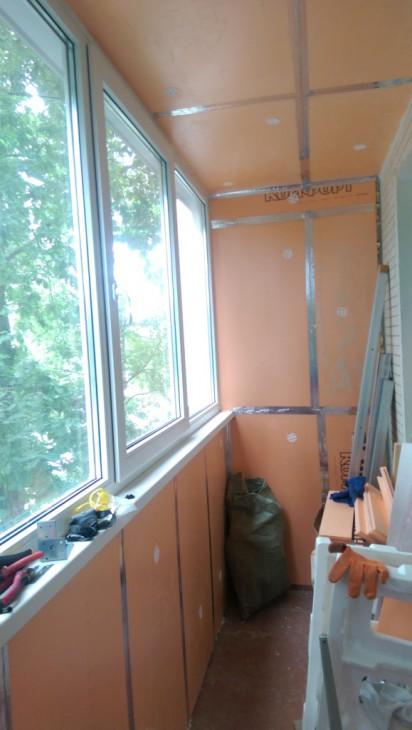 Утепленный длинный балкон с отделкой из ламината и шкафчиком